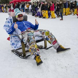 En studerande iklädd vit halare, blå jacka, tofsmössa och slalomglasögon. Han sitter i en fåtölj som är omgjord till pulka.