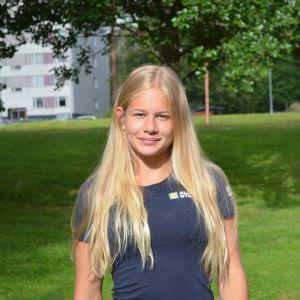 En tonårig flicka med långt hår står och ser in i kameran. I bakgrunden syns bostadshus och gräsmatta.