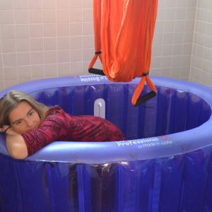 Bilden visar Piia Jokela-Nuoranen som ligger i sin förlossningsbassäng. Ovanför bassängen hänger en luftyogamatta.