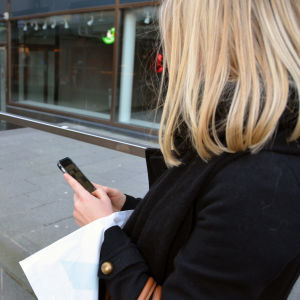 Kvinna kollar sina meddelande på sin smarttelefon.