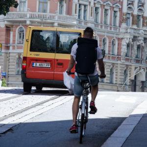 En man cyklar upp för en backe i Helsingfors.