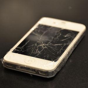 Telefon med sprucken skärm ligger på ett bord.