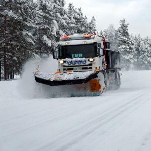 En plogbil på en snöig landsväg.