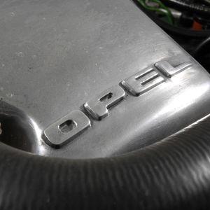Motordel med bilmärket Opel skrivet på sig.
