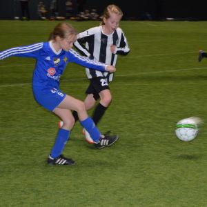 En flicka i blå spelskjorta skjuter en fotboll, medan en flicka i svartvit randig spelskjorta försöker hindra det. I bakgrunden följer en annan flicka i svartvit randig spelskjorta med händelserna.
