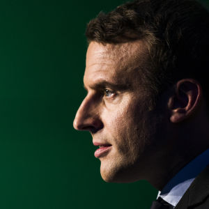 Emmanuel Macron i profil mot svart bakgrund.