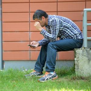 En man sitter med en mobiltelefon i handen utanför en flyktingförläggning i Sigmaringen i Tyskland.