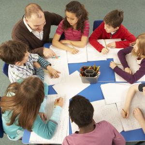 Lärare och elever samlade kring ett bord