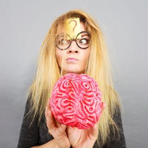 En kvinna med ett frågetecken i pannan och en finurlig min håller i en konstgjord hjärna i rosa.