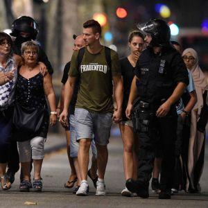 Polis i Barcelona eskorterar människor bort från området där en bil mejade ner människor den 17.8.2017.