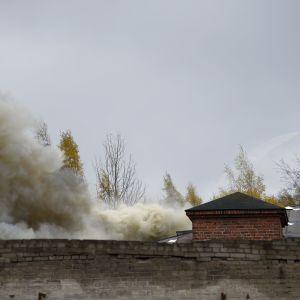 Visar tapetfabriken som brinner och en brandman som jobbar med släckningsarbete.