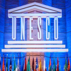 Bild från Unescos generalkonferens 2015. På bilden syns en stor, vit Unesco-logo och medlemsländernas flaggor uppställda framför den.