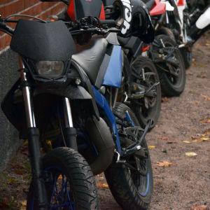 En moped står lutad mot en vägg. I bakgrunden syns fler mopeder.