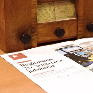 En gammal radioapparat, en dagstidning och ett datortangentbord.