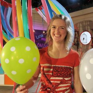 Lisa Gerkman poserar med ballonger i BUU-klubbens tv-studio