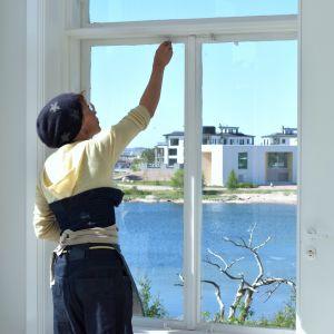 Mira Haahti öppnar ett fösnter på Tellina i Hangö. Utsikt över havet en varm sommardag.