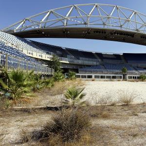 en övergiven volleybollstadion i aten. runt planen växer ogräs och läktarna är tomma.
