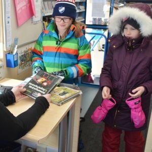 Två elever från Gammelbacka skola lånar böker från bokbussen.
