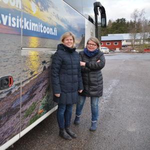 Två kvinnor står vid en buss.
