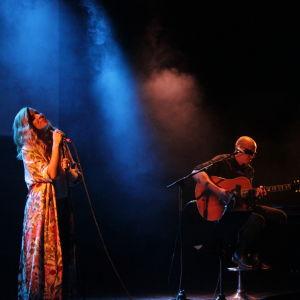 En kvinna iklädd klänning sjunger på en scen.