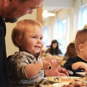 Litet barn äter skolmaten i Strömborgska skolan