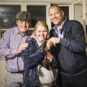 Michael Björklund och Matias Jungar står tillsammans med Karisbon Jessica Lindström som håller en svart anka i famnen.