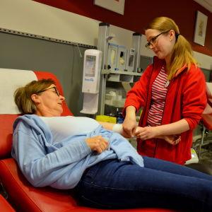 En sjukskötare lägger bandage åt Kaija Salokannel som ligger på en brits.