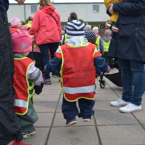 Ett litet barn i röd väst hoppar under ett motionsevenemang.