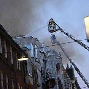 Brandman sprutar vatten på höghus som brinner på Jakobsbergsgatan i Stockholm.