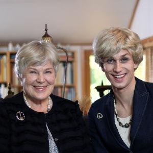 Elisabeth Rehn och Christoffer Strandberg sitter i en soffa. Christoffer Strandberg är utklädd till Elisabeth i peruk, kavaj och pärlhalsband.