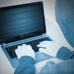 Person sitter och skriver på en dator.