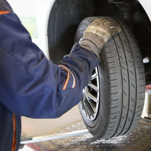En besiktningsman undersöker däcken på en bil som besiktigas.