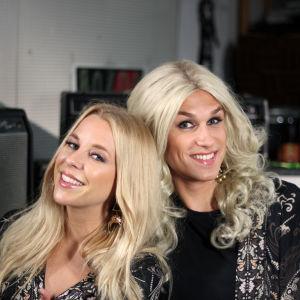 Krista Siegfrids står bredvid Kristoffer Strandberg som är utklädd till henne (med lång blond peruk).