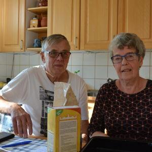 John och Birgitta Åsvik sitter i sitt kök. Birgitta bär en mörk blus och john en vit t-skjorta.