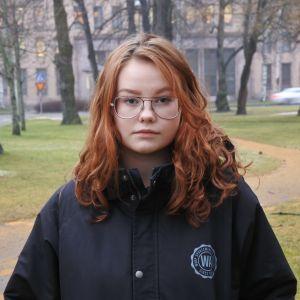 tilda eklund står i en park i höstväder. hon bär glasögon och en svart jacka.