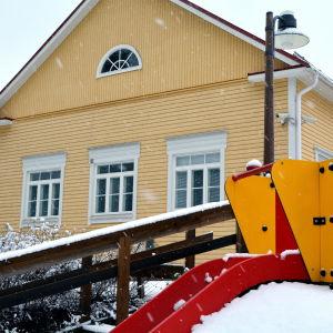 Daghemsbyggnad i lätt snöfall.
