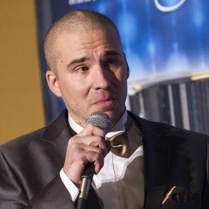 Aleksi Valavuori håller i en mikrofon.
