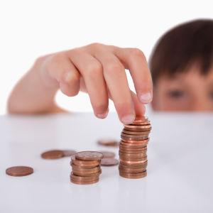Pojke staplar mynt på ett bord.