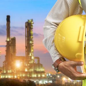 Man i gul skyddsväst med gul hjälm under armen och upplysta industribyggnader i bakgrunden. Ansiktet syns inte.