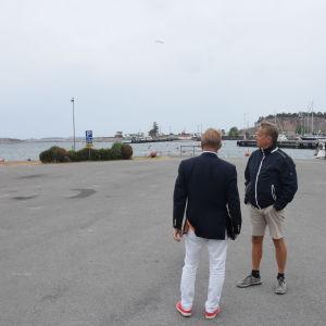 två män på parkeringsplats.