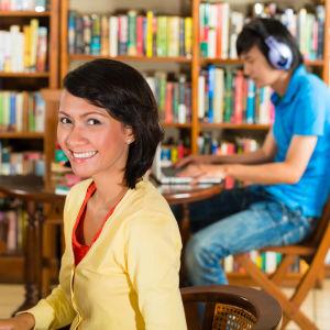 Flicka i gul skjorta sitter vid en dator i ett universitetsbibliotek.