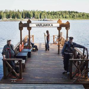Käsikäyttöinen lossi eli pieni lautta rannassa, kaksi miestä katsoo kameraa, nainen selin kameraan nojaa airoon, merta, vastarannalla horistontissa metsää.