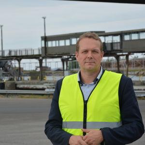 Matti Esko är vd för Kvarken ports. På bilden bär han en gul skyddsväst och står där fordon kör ombord på Wasaline. I bakgrunden ser man en gammal passagerargång, en pir och ett fraktfartyg.