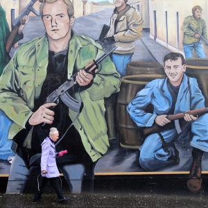 Kvinna framför en väggmålning i Nordirland.