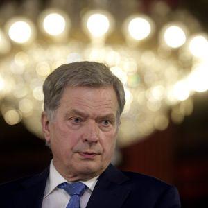 Sauli Niinistö under en kristallkrona, som lyser en gloria runt hans huvud.