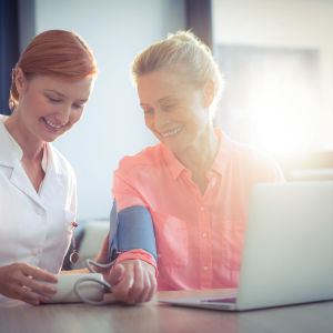 Vårdare mäter blodtryck på kvinna.