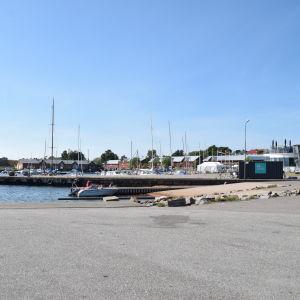 Hamn med motor och segelbåtar. Blå himmel syns i bakgrunden och röda byggnader.