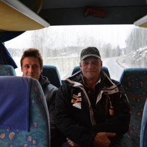 Två män på bakbänken i en buss.