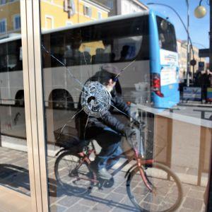 Man cyklar förbi skyltfönster med kulhål i glaset