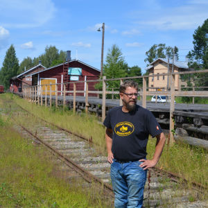 Ogräs växer mellan järnvägsspåren i Borgå, Niklas ser fundersamt på banan.